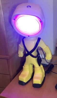 Yellow super-hero figurine in A-pose with tractor lamp head as desk lamp, shining red/blue RGB light.